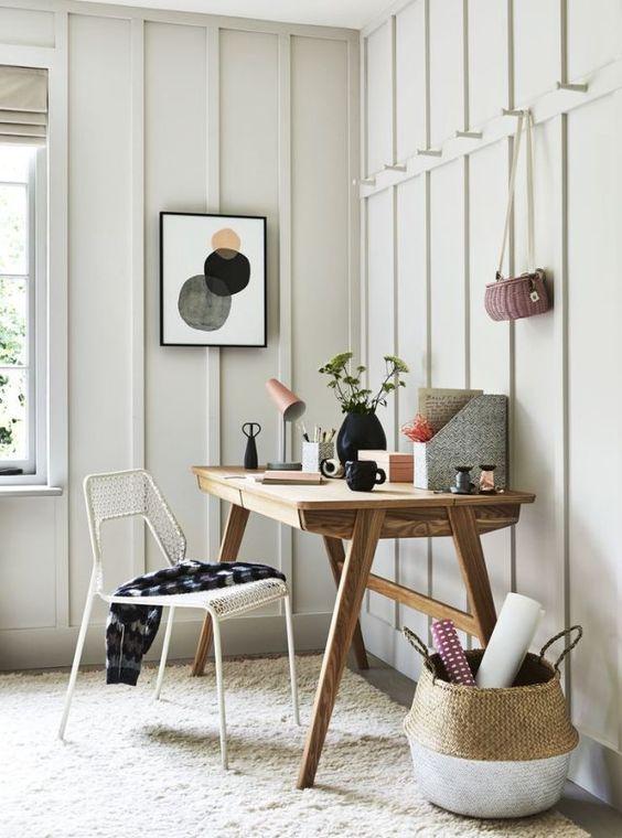 un home office neutro e accogliente con una scrivania in legno, un cestino, una sedia in filo metallico e alcune cose luminose sulla scrivania