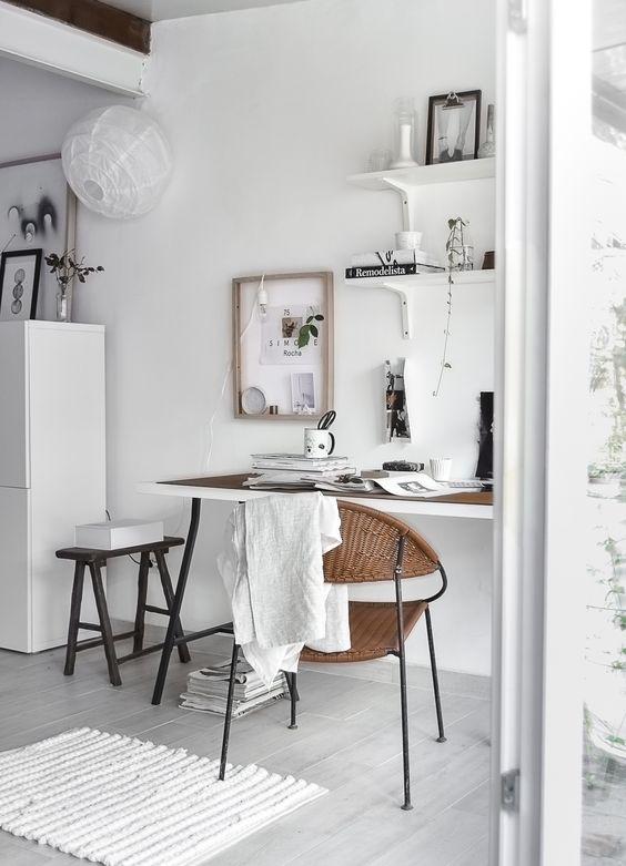 un ufficio in casa neutro mordico con una scrivania a trespolo, alcuni scaffali a parete, uno sgabello blakc e un tappeto intrecciato