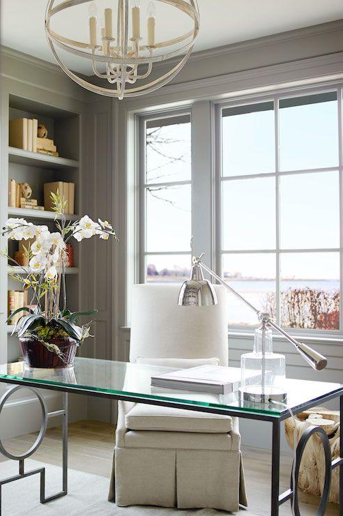 un ufficio-studio in casa neutro e super elegante in grigio chiaro, una scrivania in vetro, una sedia bianca, un lampadario da fattoria e una bella vista