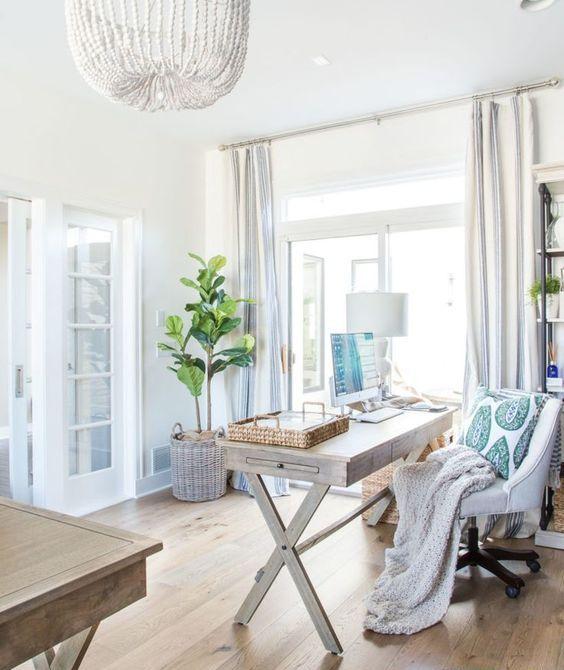 un ufficio casalingo neutro con una scrivania a cavalletto in legno, una sedia bianca, lampadari di perline in legno, tocchi di tende blu e a strisce