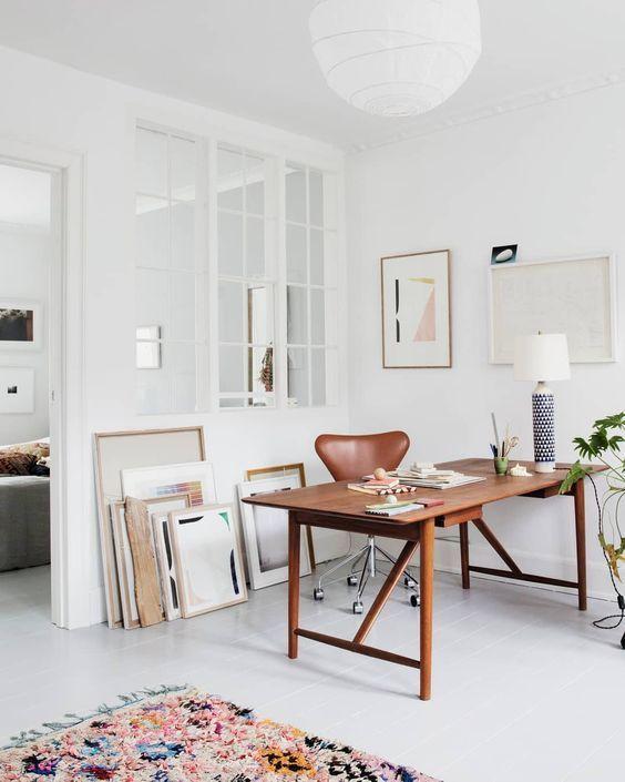 un moderno ufficio a casa neutro con una scrivania in legno dai colori intensi, una galleria a parete e alcune opere d'arte più un tappeto luminoso