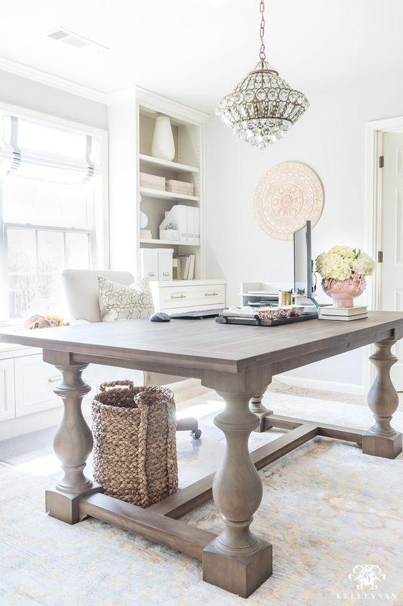 un moderno studio domestico neutro della fattoria con un lampadario di cristallo, una scrivania in legno, alcuni scaffali incorporati e una finestra con sfumature a strisce