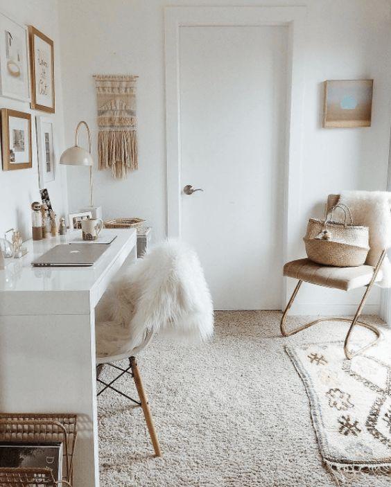 un home office boho neutro con una galleria a parete, una scrivania bianca, tappeti a strati e un appeso in macramè sembra rilassante