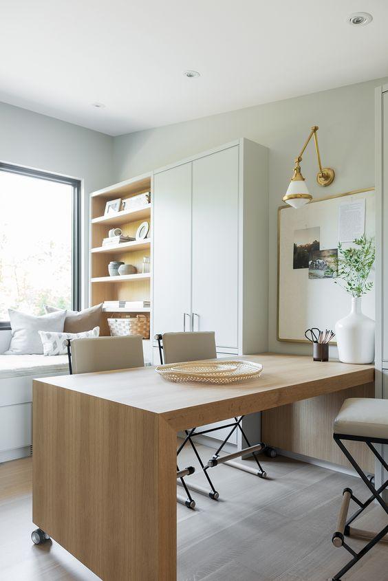 un home office neutro e minimalista in grigio tortora, con una grande scrivania in legno, un armadio e un mobile contenitore e un divano-letto con finestra