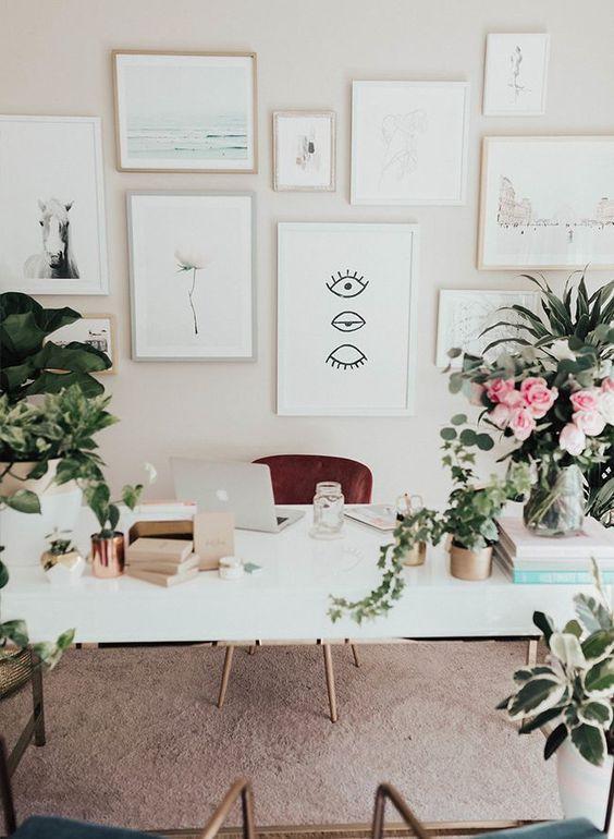 un ufficio domestico semplice e neutro con una galleria a parete neutra, fiori in vaso e vegetazione e una grande scrivania bianca