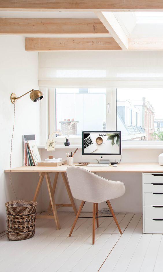 un ufficio in casa scandinavo neutro con una scrivania in legno, sgabelli in legno e sughero, una lampada a sospensione e alcune opere d'arte in bianco e nero