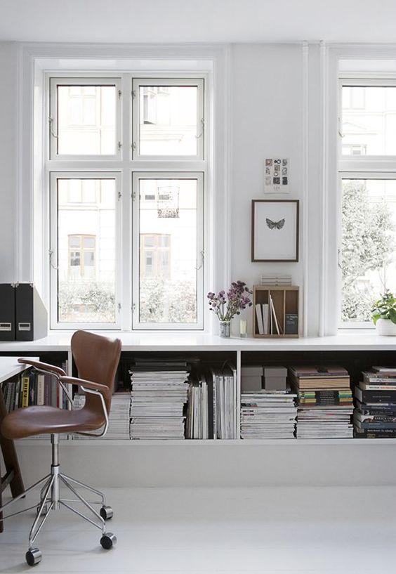 un semplice ufficio bianco minimalista con un grande contenitore aperto, una scrivania bianca e una sedia in pelle marrone