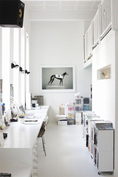 un studio in casa bianco condiviso con molti armadietti, una scrivania condivisa, alcune opere d'arte e lampade e molta luce