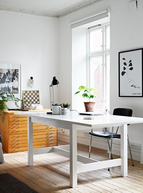 un ufficio domestico moderno e neutro con una scrivania bianca, un armadietto in legno, alcune opere d'arte in bianco e nero e una sedia nera