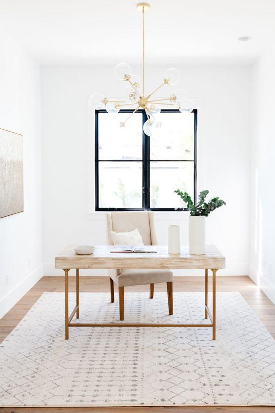 un ufficio domestico neutro semplice e chic con una piccola scrivania, una sedia comoda, un lampadario dorato, un tappeto stampato e una finestra con cornice nera