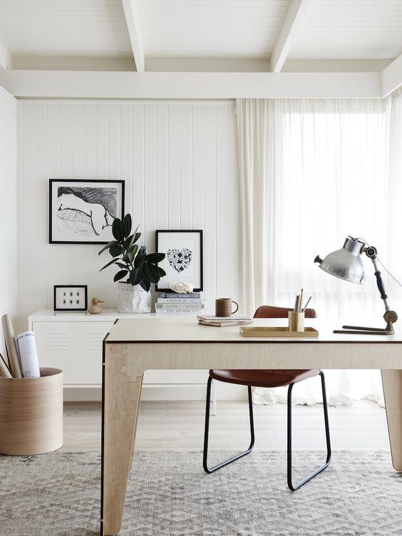 un elegante home office neutro con una scrivania in compensato, un armadio a muro, una sedia in pelle, alcune opere d'arte