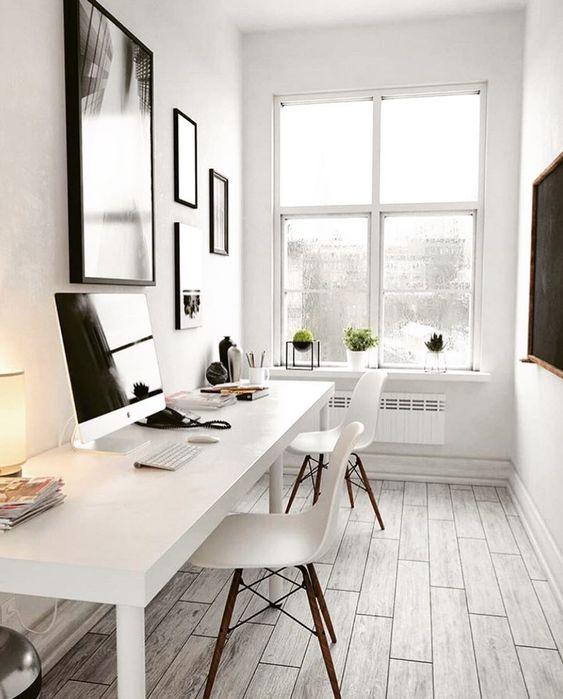 un ufficio molto neutro e piccolo con una scrivania bianca condivisa, sedie bianche, una galleria a parete con opere d'arte in cornici nere