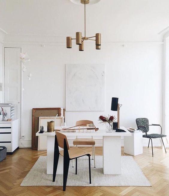 un elegante moderno ufficio a casa con una scrivania wihte, sedie in compensato, alcune opere d'arte e tocchi di bronzo qua e là