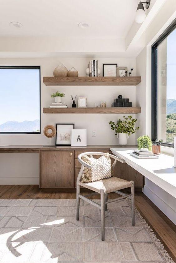 un accogliente ufficio in casa neutro con viste meravigliose e due scrivanie, mensole in legno e una sedia comoda, molta luce naturale