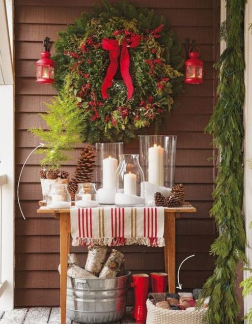 una consolle con candele a colonna, pigne, una ghirlanda sempreverde con bacche rosse e fiocchi, lanterne rosse e legna da ardere in un secchio