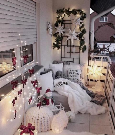 un piccolo balcone accogliente con un albero luminoso con fiocchi rossi, alcune lanterne a candela, una lampada a stella, stelle e vegetazione sul muro e pelliccia e tessuti a maglia