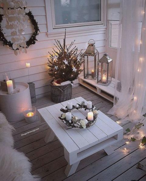 un piccolo e accogliente balcone invernale con mobili da nave, pelliccia sintetica, candele nei candelabri e lanterne a candela, un mini albero con stelle e una ghirlanda