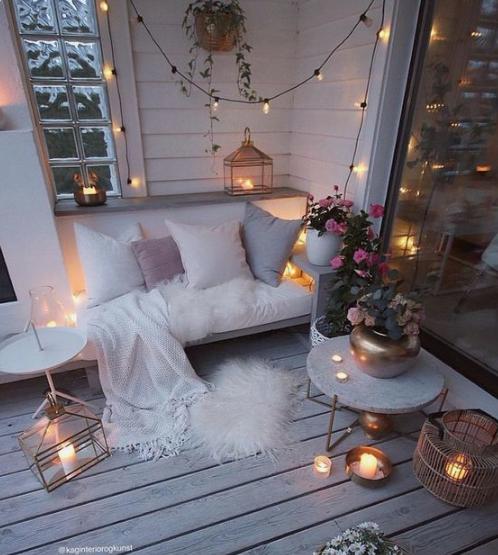 un accogliente balcone invernale con finta pelliccia, candele in lanterne e candelabri, luci e fiori in vaso