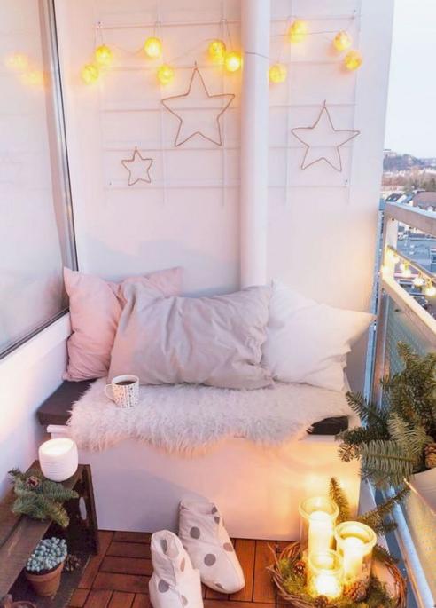 un piccolo balcone invernale con molte luci, decorazioni a stella, pelliccia sintetica, cuscini pastello, candele, pigne e sempreverdi