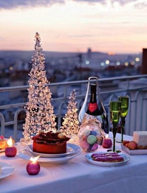 servire champagne e dolci solo per voi due in balcone e decorare la tavola con alberi di Natale e candele