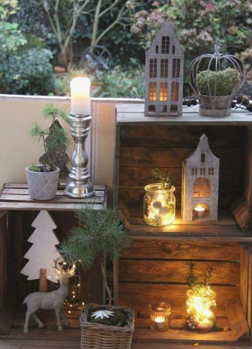grazioso balcone invernale con casse, lanterne a candela, muschio e sempreverdi, cervi e alberi di compensato