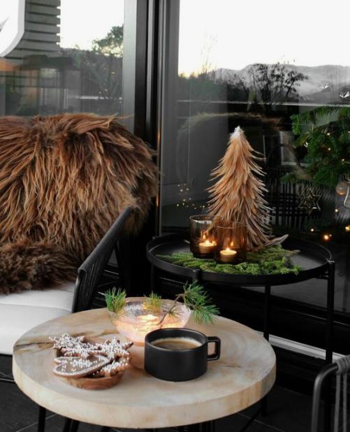 tavolini con sempreverdi, un mini albero di Natale, candele in candelabri scuri e coperte di pelliccia sintetica sulle sedie