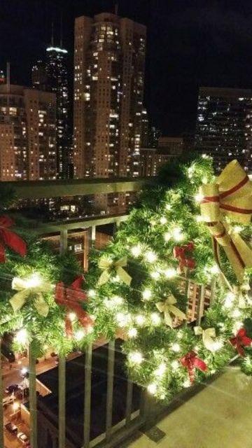 una ghirlanda verde e una ghirlanda con luci e fiocchi rossi e oro per decorare il balcone per le vacanze