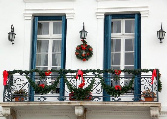 ghirlande verdi, fiocchi rossi, una ghirlanda verde con fiocchi e persiane blu conferiscono al balcone un aspetto luminoso da vacanza