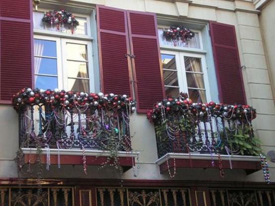 mini balconi decorati con molti ornamenti natalizi, ghirlande di perline, fogliame lussureggiante e fiori per una forte sensazione di vacanza,