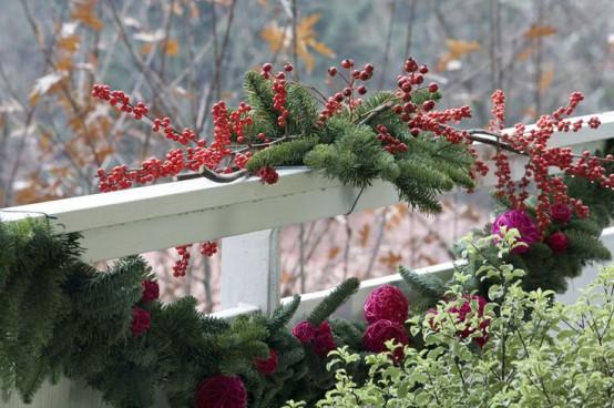 vegetazione lussureggiante, sempreverdi, bacche e ornamenti natalizi rossi per decorare il balcone per le vacanze con un'atmosfera naturale