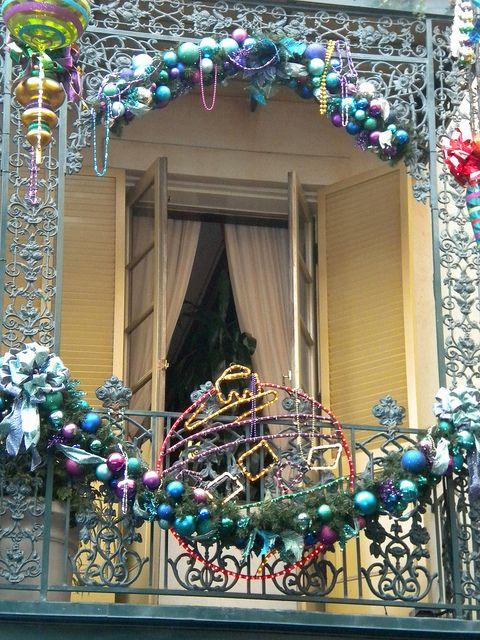 un balcone completamente decorato con addobbi natalizi colorati, fiocchi, sempreverdi e ornamenti fatti di luci