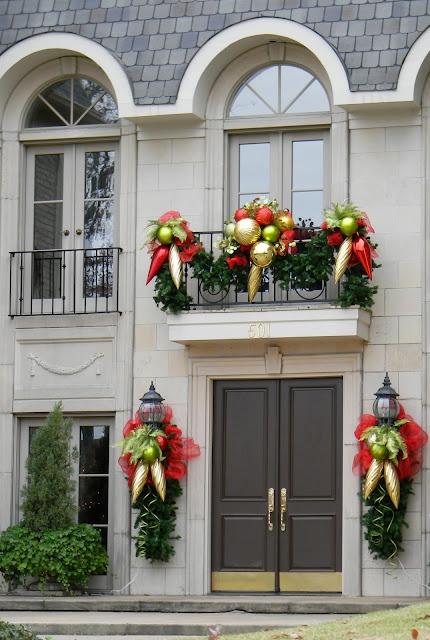 arredamento luminoso balcone vacanza fatto con sempreverdi, oro di grandi dimensioni, ornamenti verdi e rossi e fiocchi rossi