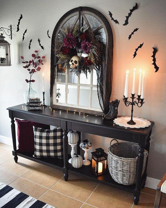 una console d'ingresso di Halloween con zucche, pipistrelli sul muro e una ghirlanda di fiori scuri con un teschio per un tocco lunatico