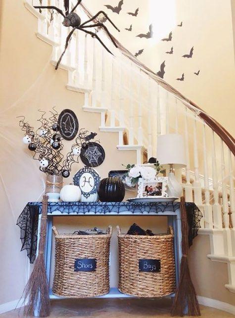 una consolle ricoperta da una tovaglia a ragnatela nera, zucche bianche e nere, ornamenti e piatti