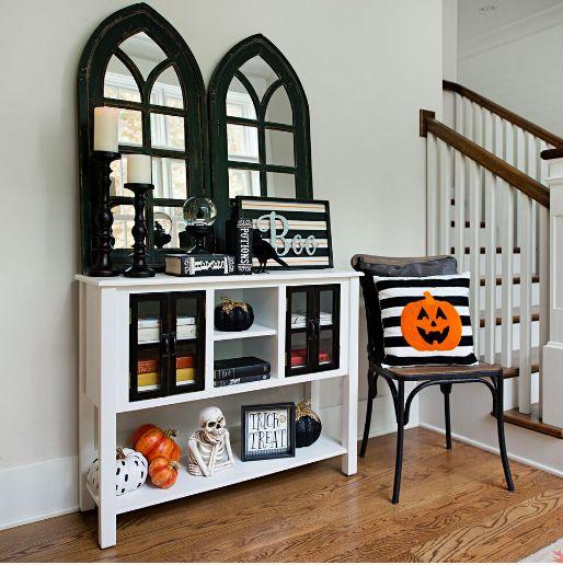un luminoso ingresso di Halloween con scheletri, zucche, segni e un cuscino di zucca è facile da realizzare
