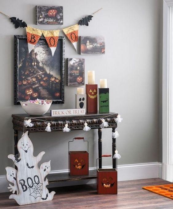 un ingresso chic di Halloween con un bizzarro muro di galleria, ghirlande di nappe, fantasmi, lanterne di zucca, un pavese di stoffa