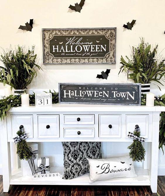 una console da ingresso semplice e fresca di Halloween con cuscini bianchi e neri, arrangiamenti di vegetazione, insegne e candele è chic