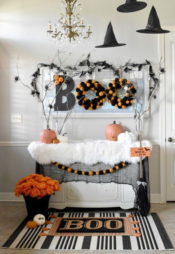 una console da ingresso di Halloween con un tappeto stampato, un'audace composizione floreale, ghirlande di pompon, rami con ragni e cappelli da strega