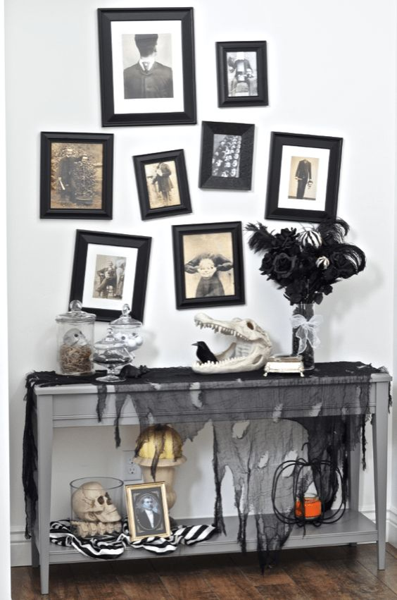 una console di Halloween con tulle nero, teschi di animali e umani, una spettrale parete della galleria e una composizione di piume nere