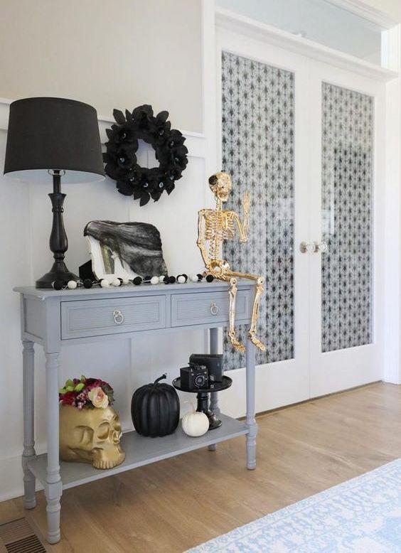 una console d'ingresso decorata con un teschio gigante, uno scheletro d'oro, zucche bianche e nere, una ghirlanda nera e tulle