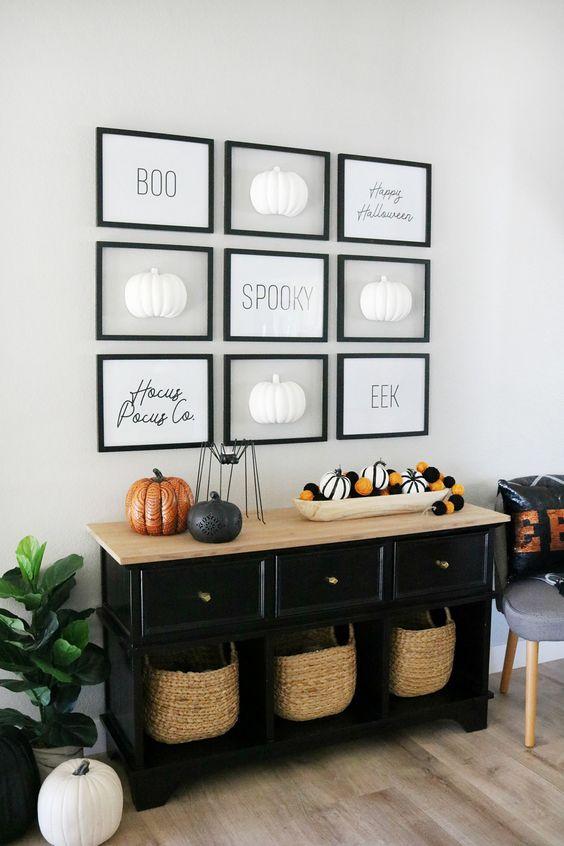 una console d'ingresso di Halloween con zucche a strisce e nere e arancioni, una galleria a parete con zucche e parole