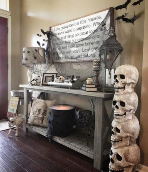 una console rustica con pipistrelli e ragni neri, ragnatela nera e un calderone illuminato e teschi