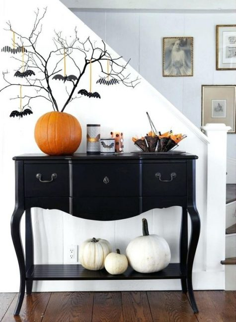 un'elegante consolle nera con zucche bianche, una zucca arancione come vaso, rami neri con pipistrelli e portacandele a pipistrello