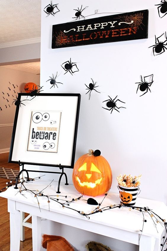 una console d'ingresso di Halloween con una zucca di Halloween, un cartello, alcuni ragni e arte e un ramo inquietante