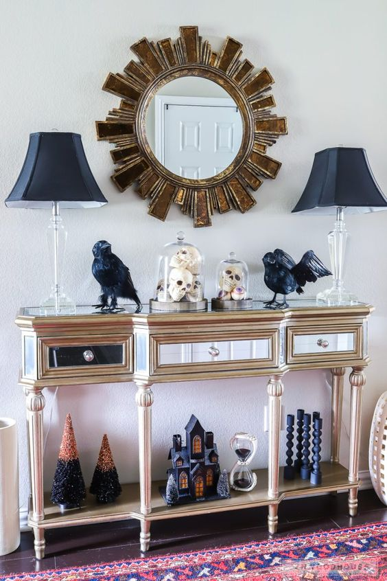 una raffinata consolle da ingresso con lampade nere, merli, candelabri neri, una casa nera e alberi di Halloween