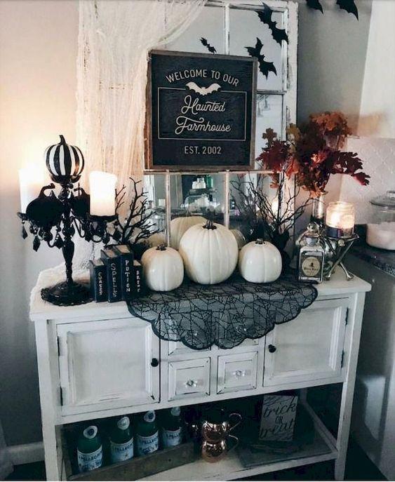 una console da ingresso bianca con zucche bianche, pizzo nero, zucche bianche e nere, candele e una composizione di foglie autunnali