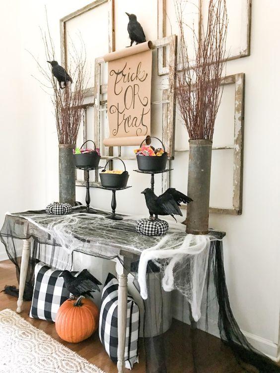 un ingresso di Halloween con ragnatela, cuscini a quadri, una zucca, merli, rami in secchi e cornici vuote