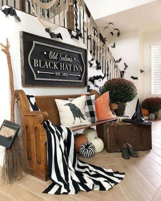 uno splendido ingresso di Halloween con grandi zucche, tessuto bianco e nero, una scopa da strega, un cappello, scarpe e alcuni pipistrelli
