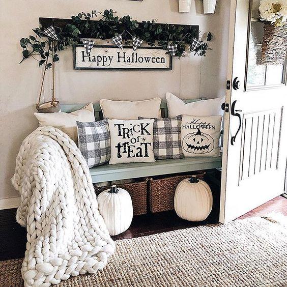 un ingresso di una fattoria vestito per Halloween con cuscini di Halloween, un cartello e un po 'di verde scuro