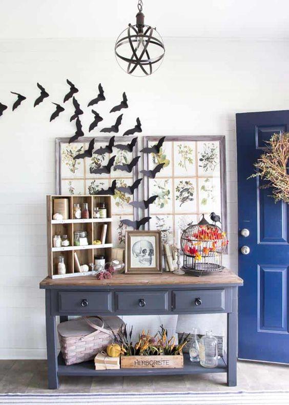 un ingresso vintage di Halloween con pipistrelli, un segno di teschio e una gabbia nera con un finto merlo creano un'atmosfera qui